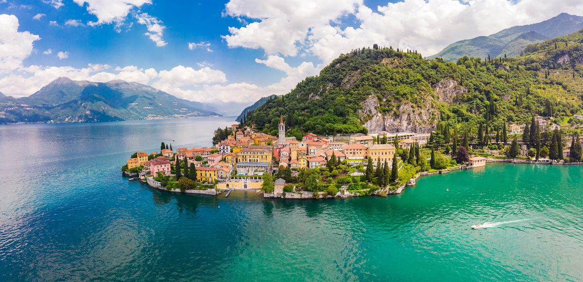 Beautifull Aerial Panoramic View From The Drone To The Varenna Famous Old Italy Town On Bank Of Como Lake. High Top View To Water Landscape With Green Hills, Mountains And City In Sunny Summer Day.